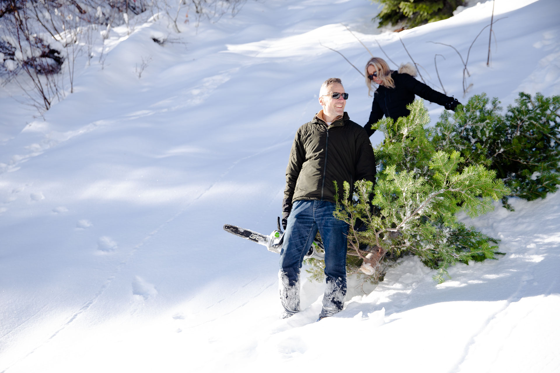 Man and wife coming down a snowy hill after cutting their Christmas tree down