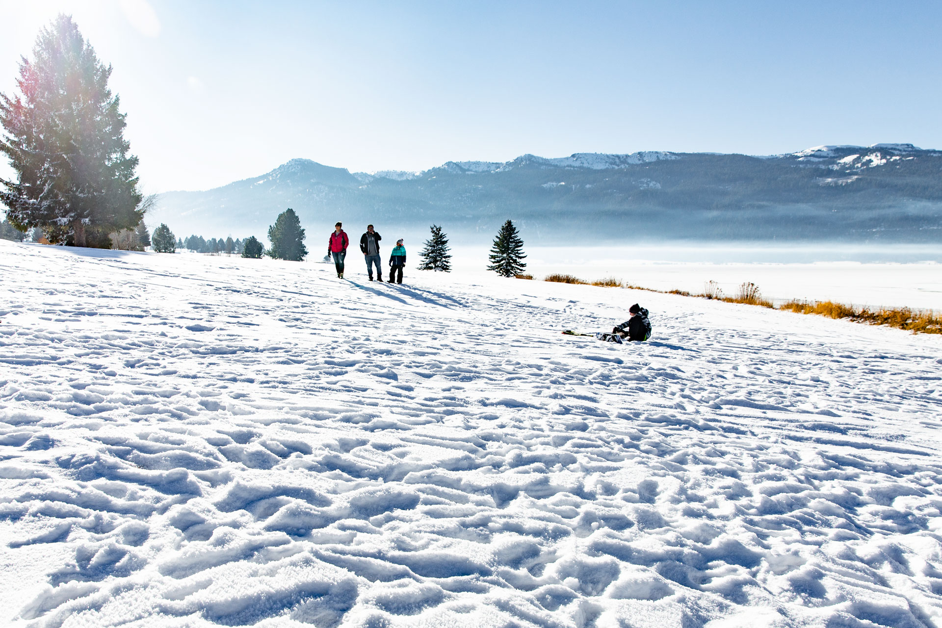 family of four hanging out around the lake in the snow while sledding