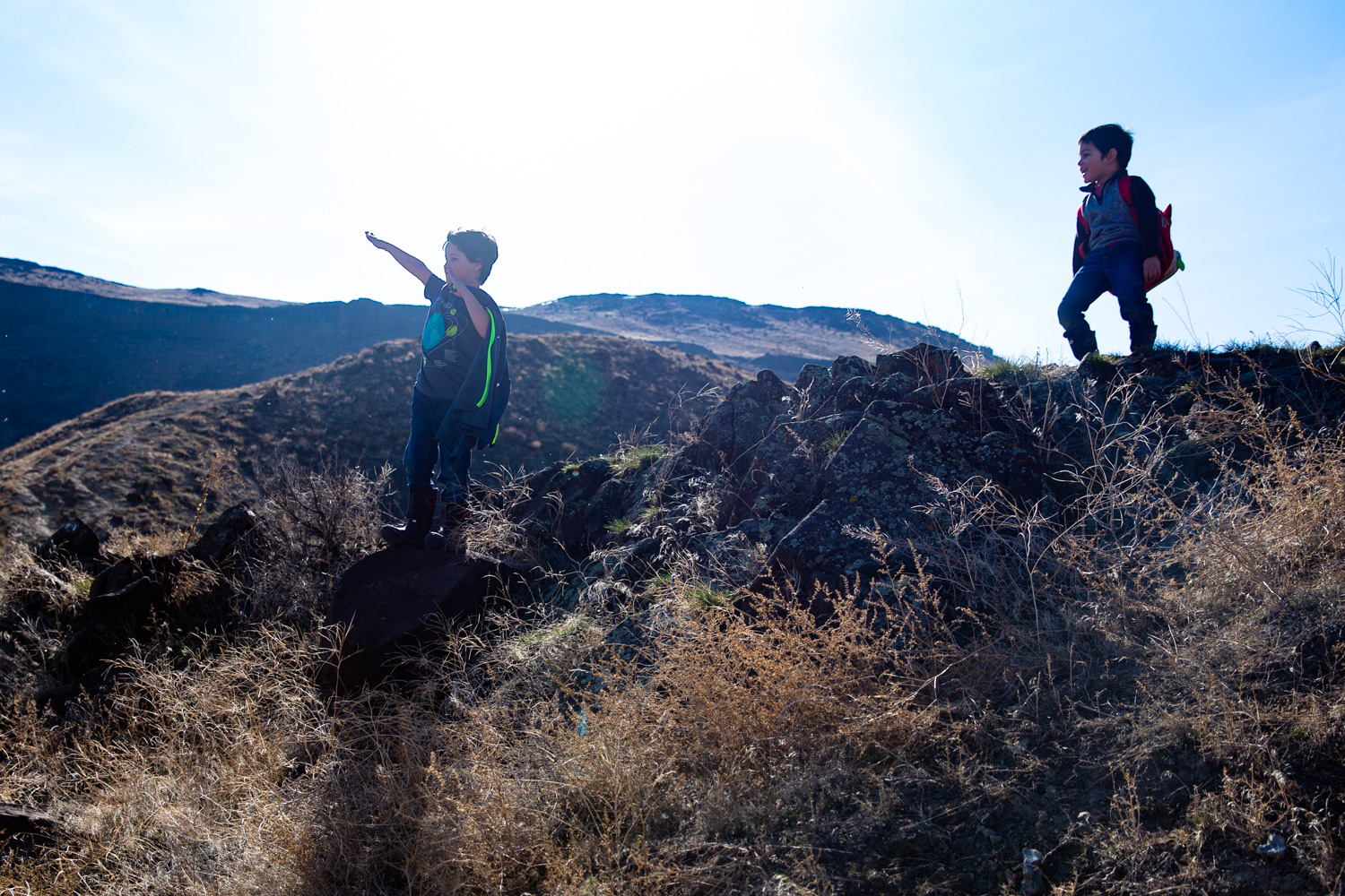 Two boys climbing on rocks as one boy acts like Superman at the top